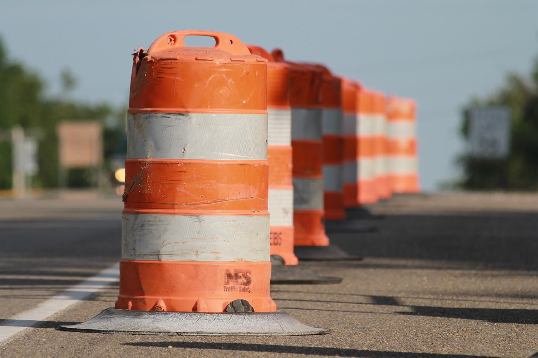 Orange road construction cones on an asphalt road.